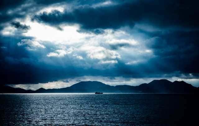 暗雲垂れ込めた海に漂うボート